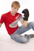 Jovem estudante rapaz vestido em vermelho ouvindo música de mp3, estúdio isolado no branco — Foto Stock