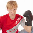 Angry young man in a red t-shirt with a boxing glove — Stock Photo