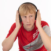 Upset young student hearing music on white — Stock Photo