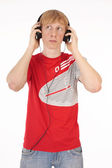 Young man in the red t-shirt with headphones on a white background — Stock Photo