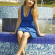 Beautiful woman in blue dress standing near big fountain — Stock Photo #9484467