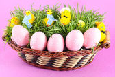 Beautiful easter basket with chicken and decorated eggs in green grass — Stock Photo