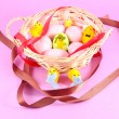 Easter basket filled with eggs and with chicken on pink background — Stok Fotoğraf #9663737