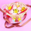Easter basket filled with eggs and with chicken on pink background — Stock fotografie #9663737