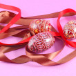 Colorful easter eggs , with a ribbon , on a pink background — Stock Photo