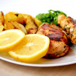 Roast chicken with baked potatoes, lemons and green — Stock Photo