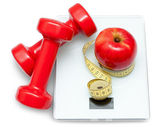 Scales, dumbbells, red apple and measuring tape — Stock Photo