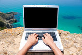 Hands with laptop at the beach — Stock Photo