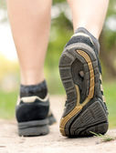 Woman walking on hiking trail in forest — Stock Photo