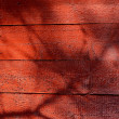 Shadows on red-painted wooden wall. — Stock Photo