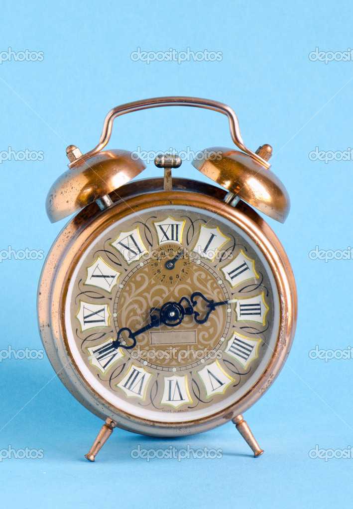 Retro vintage clock with roman numbers on blue background. Ancient old object. — Stock Photo #10557306