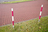 Tiled park lane and protective barrier stakes — Stock Photo