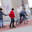 Teenagers ride bike and skateboard. Bicycle trail. — Stock Photo #8254288
