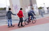 Teenagers ride bike and skateboard. Bicycle trail. — Stock Photo
