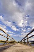 Lange houten plank brug over het meer en bewolkte hemel. — Stockfoto