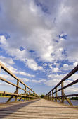 Long wooden plank bridge over lake and cloudy sky. — ストック写真