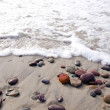 Sea waves beat stones lying in sand on coast line. — Stock Photo