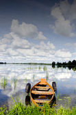Boat moored rubber tires cloud reflection on water — Stock Photo
