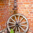 Antique wooden carriage wheel and kerosine lamp - Stock Photo