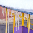 Melting icicles spring on roof playground house. — Stock Photo