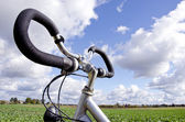 Bicycle handlebar on cloudy sky. No fuel needed — Stock Photo