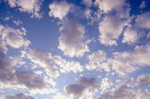 Cloudy blue spring sky sun-lit background — Stock Photo