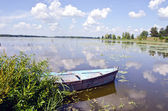 Spring lake fragment. Old boat moored on shore. — Stock Photo