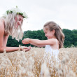 Stock Photo: Mother and daughter playing at corn