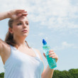 Beautiful girl drinking water against blue sky — Stock Photo