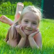 Happy little girl lying at the park — Stock Photo