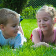 A smiling boy and a little girl are lying on the grass in the park — Stock Photo