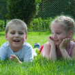 Smiling boy and little girl are lying on grass in park — Stock Photo #10623135