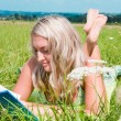 Stock Photo: Beautiful young girl on the meadow with a book