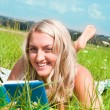Beautiful young girl on the meadow with a book — Stock Photo #10624463