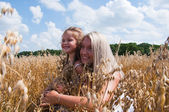 Mother and daughter playing at corn — Stock Photo