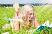 Beautiful young girl on the meadow with a book — Stock Photo