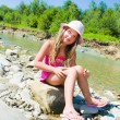 Cute little girl playing on the river — Stockfoto