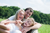 Playful family on the meadow — Stockfoto