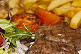 Grilled steak with chips and salad — Stock Photo