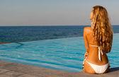 Beautiful woman in white bikini sitting near infinity pool — Stock Photo