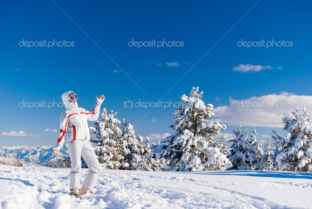 Cheery skier standing on the top of mountain  Stock Photo #8454388