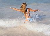 Sexy woman running in waves on caribbean beach — Stock Photo