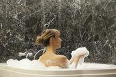 Beautiful young woman taking foam bath — Stock Photo