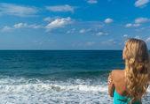 Sexy woman on a beach looking far on horizon — Stock Photo