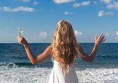 Woman in white dress near sea looking far — Stock Photo