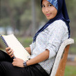 Beautiful young muslim lady smile while sit at the park — Stock Photo