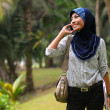 Beautiful young muslim lady smile while talk to phone — Stock Photo #8816837