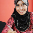 Beautiful young muslim smile while writing infront of notebook — Stock Photo