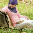 Beautiful young muslim lady lean again the tree stump reading — Stock Photo