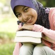 Beautiful young muslim lady holding book — Stock Photo